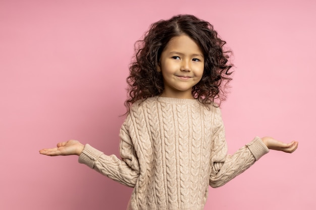 의아해 귀여운 곱슬 어린 소녀 아이 손을 옆으로 제기, 두 손바닥에 copyspace 들고, 선택, 결정, 포즈. 무엇을 선택해야할지 모르겠습니다.