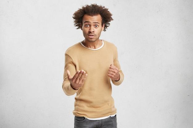 어리둥절한 어두운 피부의 남성이 누군가를 비난하고 주먹으로 위협하고 캐주얼 스웨터를 입습니다.