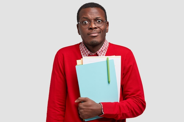 Puzzled dark skinned man carries notepad, looks with frustrated expression