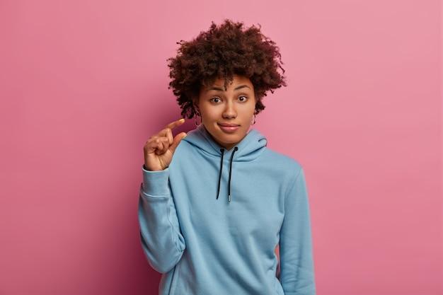 困惑した暗い肌の女性は、小さなサイズのアイテムを形作り、小さな看板を示し、青いパーカーを着て、印象に残っていないように見え、ピンクのパステルカラーの壁に隔離されています。人とボディーランゲージの概念