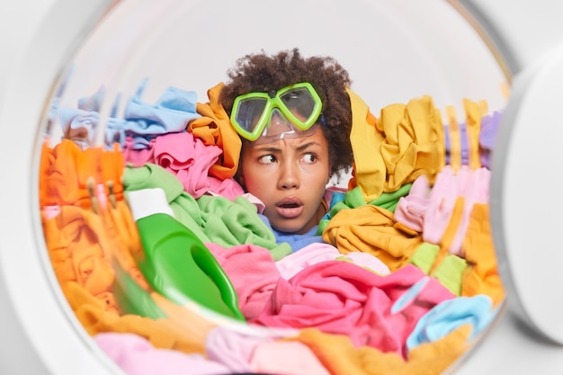 Puzzled displeased afro american woman looks indignant away wears snorkeling mask drowned in big heap of laundry loads washing machine with clothes has much household duties and responsibilities