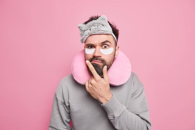 의아해 불쾌한 수염 난 남자가 턱에 손을 대고 뭔가가 이마에 눈가리개를 끼는 것을 좋아하지 않는다 목 주위의 여행 베개 캐주얼 점퍼가 미용 절차를 겪고 눈 밑에 패치를 적용