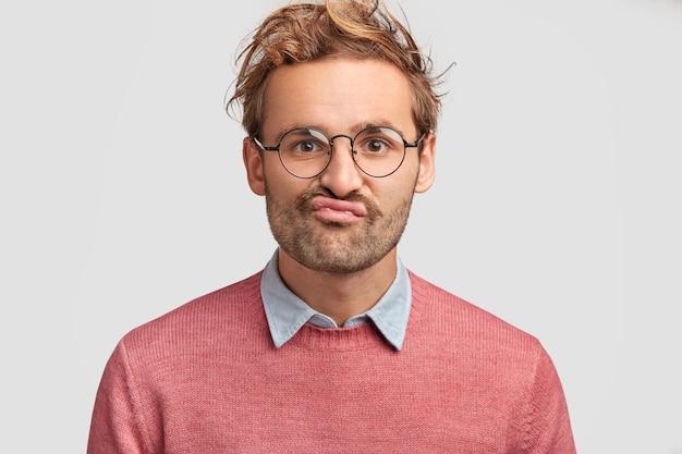 困惑した不機嫌な男は唇を曲げ、カメラを疑わしく見て、ためらいを感じ、ピンクのセーターを着て、巻き毛をして、白い壁にポーズをとる