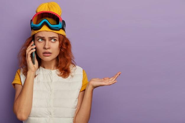 의아해 불만족 한 여자는 귀 근처에 휴대 전화를 보유하고 손바닥을 제기하고 보라색 벽, 빈 공간에 포즈를 취합니다.