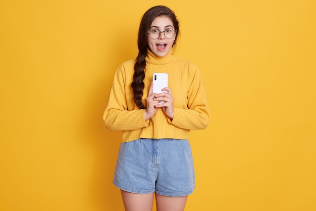 Puzzled emotional dark haired woman holds smart phone, opens mouth widely, astonished by something impressive, posing isolated on yellow wall, wearing pullover and jeans short.
