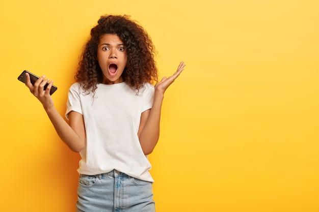 의아해 감정적 인 어두운 피부 여자는 스마트 폰을 보유하고 입을 넓게 열고 흰색 티셔츠를 입고 노란색 스튜디오 벽에 고립 된 당황과 함께 손바닥을 올립니다.