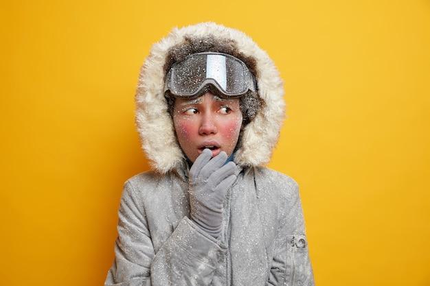 얼음으로 덮인 얼굴을 가진 의아해 민족 여성은 서리가 내린 날씨에 겨울 재킷 장갑을 끼고 차가운 외모를 느낍니다.