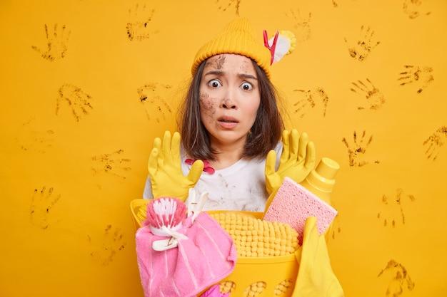 困惑した興奮したアジアの主婦が散らかった部屋を見つめる何から始めればいいのかわからない停止ジェスチャーで手を上げる帽子をかぶるゴム手袋がいっぱいの洗濯かごの近くでポーズをとる