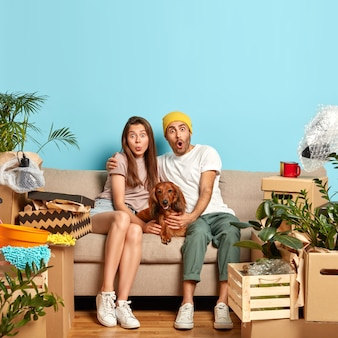 Puzzled family couple sit together near dog on couch, rent new flat, move in apartment, gazes with shock, have day of relocation, surrounded with personal stuff in boxes. new home and moving.