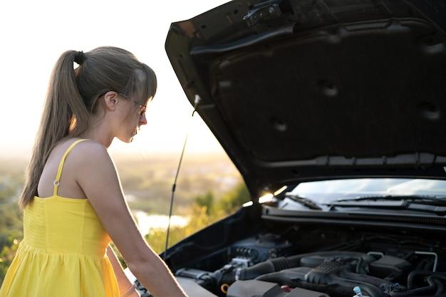壊れたエンジンを検査するポップアップフードで彼女の車の近くに立っている困惑した女性ドライバー。