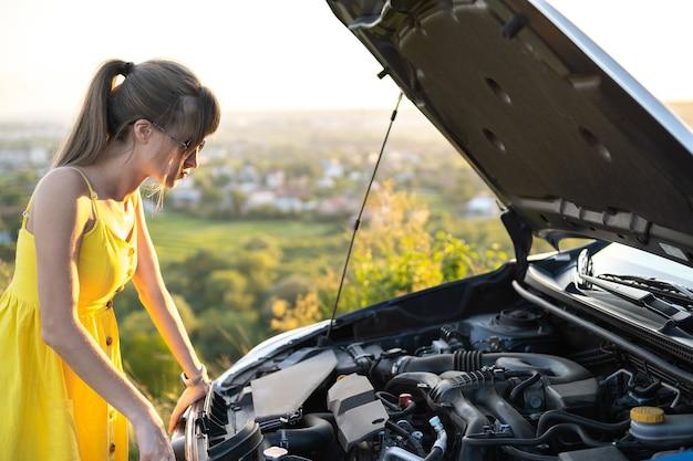 壊れたエンジンを見ているポップアップフードで彼女の車の近くに立っている困惑した女性ドライバー。