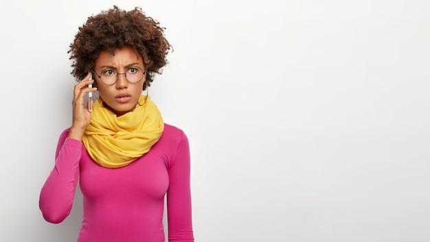 Modello femminile perplesso scontento con una cattiva connessione mobile, riceve notizie spiacevoli tramite telefono cellulare