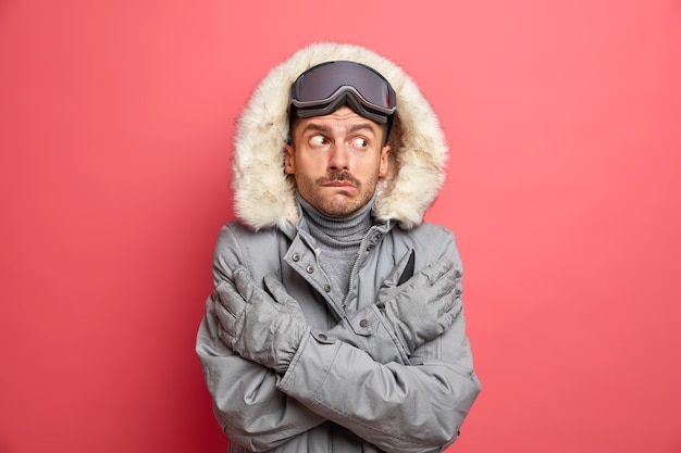 Puzzled frozen man crosses hands and tries to warm himself trembles from cold during snowy low temperature weather wears warm winter jacket gloves and ski goggles shaking freezing on frosty day