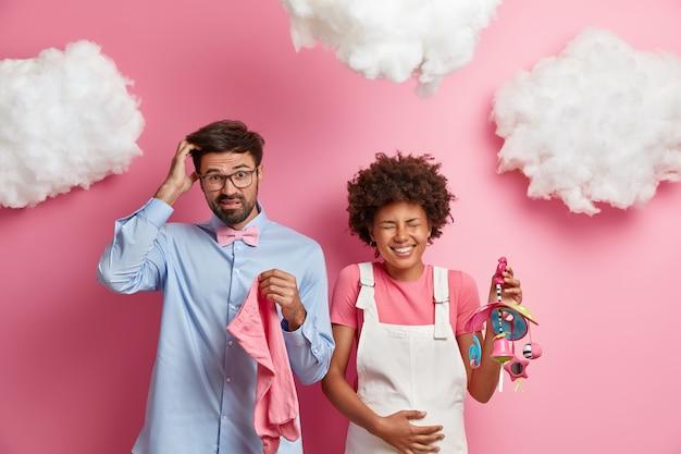 어리둥절한 미래의 아버지는 태어나지 않은 아이를 위해 어떤 옷을 사야할지 모르기 때문에 머리를 긁고, 기뻐하는 임산부는 배를 만지고, 아기 모바일을 안고, 긍정적 인 감정을 표현하고, 곧 부모가됩니다.