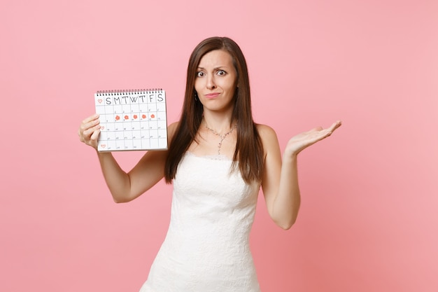 Puzzled guilty woman in white dress spread hand hold female periods calendar for checking menstruation days