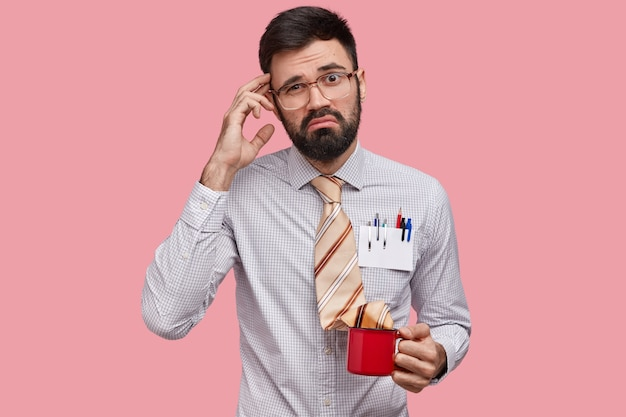 Puzzled heistant unshaven man scratches head, has displeased expression, wears elegant shirt, has tie in cup of drink, has no idea, isolated over pink space