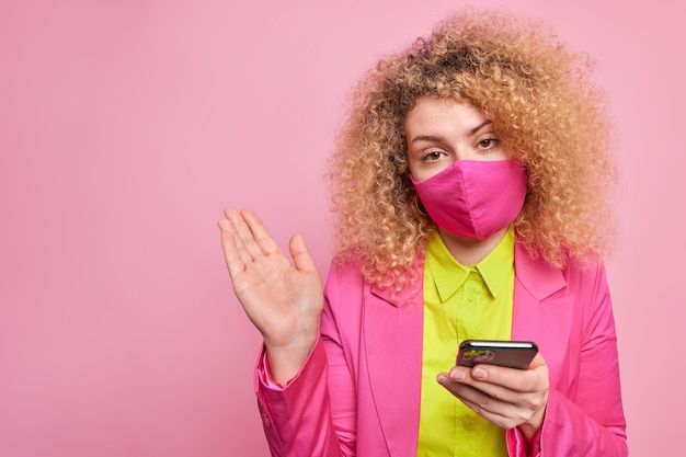 Puzzled hesitant curly haired woman dressed in bright formal clothes prepares for business meeting wears protective mask during quarantine checks newsfeed via smartphone isolated on pink wall