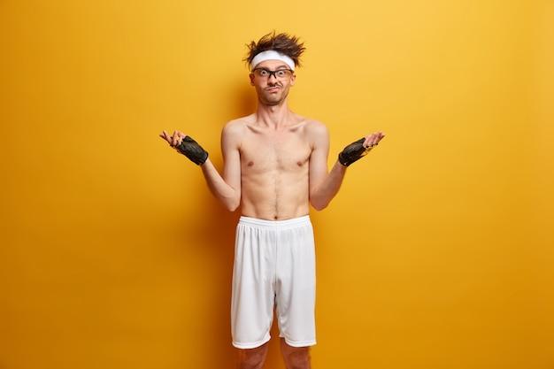 L'uomo esitante perplesso allarga le mani e resta confuso, indossa una fascia bianca, guanti sportivi e pantaloncini bianchi, ha un allenamento o un allenamento fitness, posa con il torso nudo contro il muro giallo
