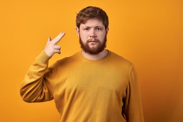 Озадаченный нерешительный рыжий мужчина держит подбородок и поднимает бровь с невежественным выражением лица, не может принять решения, о чем-то размышляет, одет в повседневную белую футболку