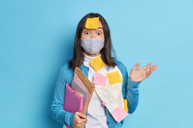 Puzzled hesitant woman entrepreneus works distantly from home being on self isolation wears protective mask from coronavirus overloaded with paper work organizes daily schedule. office work.