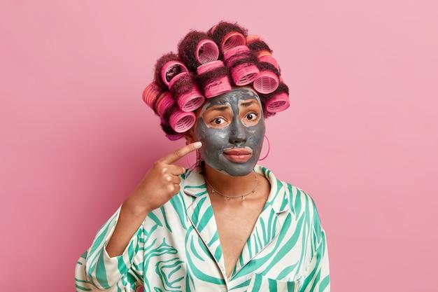 Озадаченная домохозяйка проходит косметические процедуры, у нее проблемные точки кожи на глиняной маске на лице уменьшает мелкие морщинки, применяет валики для прически, носит халат, изолированный на розовой стене