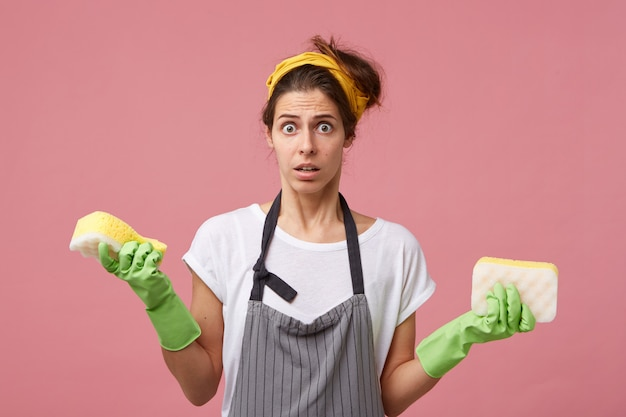 Casalinga perplessa che indossa sciarpa gialla sulla testa, grembiule, guanti di gomma protettivi che tiene due spugne ordinate che hanno uno sguardo insoddisfatto e sorpreso mentre va a pulire il suo appartamento. faccende domestiche