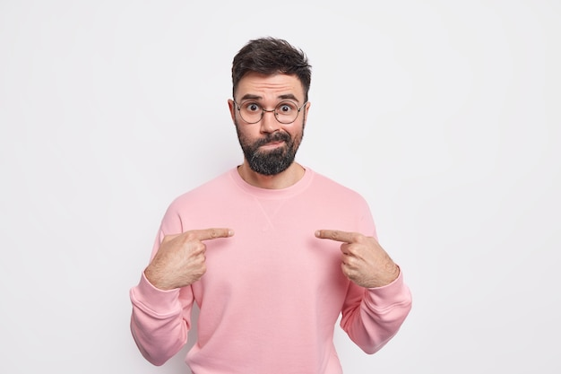 Puzzled indignant bearded young man indicates at himself asks why me purses lips wears round spectacles poses against white wall surprised being chosen. negative human reactions concept