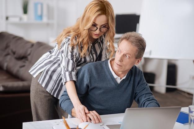 일하는 동안 사무실에 앉아 여성 동료의 행동에 대한 부정적인 태도를 표현하는 성숙한 사무실 관리자
