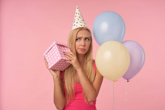 Signora bionda dai capelli lunghi perplessa con acconciatura casual tenendo presente la scatola nelle mani e cercando di scoprire cosa c'è dentro, festeggia il compleanno con palloncini multicolori, in posa su sfondo rosa