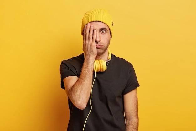 困惑した男性モデルは倦怠感からため息をつき、顔の半分を覆い、意外と片目で見える