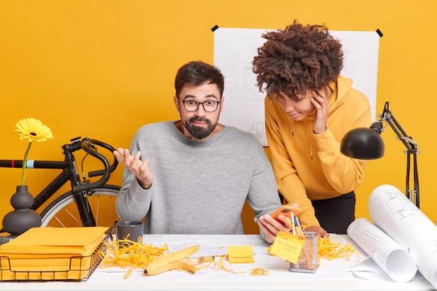 困惑した男と彼の同僚または研修生は憤慨しているように見え、デスクトップでポーズをとり、計画やアイデアについて話し合い、スケッチを作成し、青写真を研究して建築プロジェクトを準備します。コラボレーションのコンセプト
