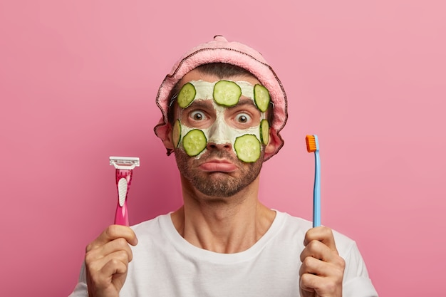 Puzzled man applies nourishing cleansing mask, holds toothbrush and razor, going to shave and brushing teeth, dressed in casual clothes, poses against pink space. men