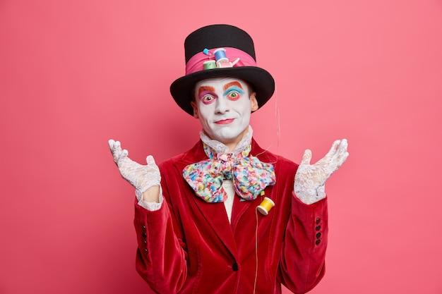 어리둥절한 남자는 미친 티 파티가 우둔한 몸짓으로 손을 들게할지 망설입니다. 축제 의상을 입고 분홍색 벽에 모자 포즈를 취합니다.