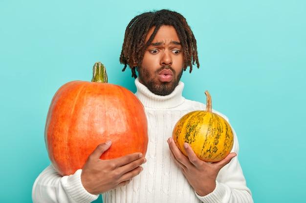 Озадаченный мужчина держит две тыквы, выбирает, какая из них лучше для приготовления здоровой и питательной еды, носит белый свитер с длинным воротником.