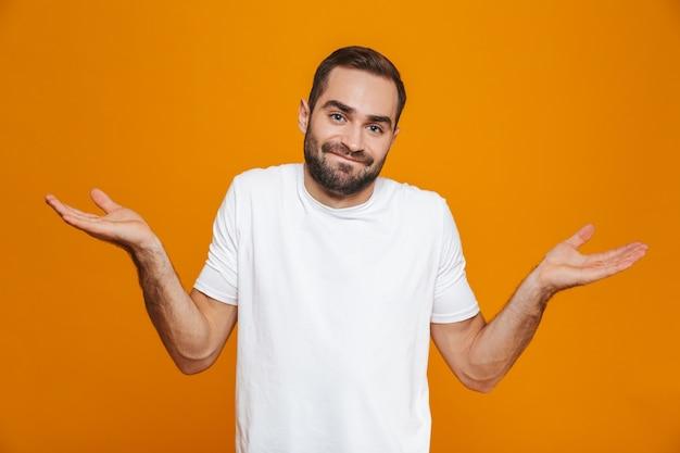노란색에 고립 된 손을 던지는 t- 셔츠에 의아해 남자