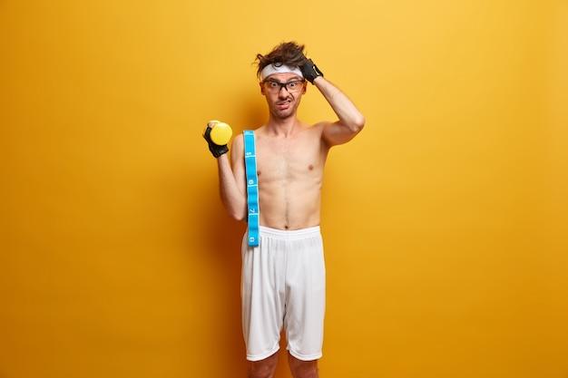 의아해하는 남자는 머리를 긁고, 체중 감량을 위해 아침 운동을하고, 아령으로 손을 들고, 어깨에 측정 테이프를 들고, 노란색 벽에 흰색 반바지에 벌거 벗은 몸통으로 포즈를 취합니다.