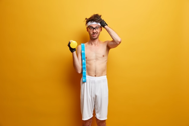Puzzled man scratches head, does morning exercises for weight loss, raises hand with dumbbell, carries measuring tape on shoulder, poses with naked torso in white shorts against yellow wall.