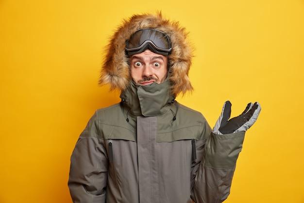 L'uomo perplesso in abito invernale alza la mano e sembra confuso, indossa il cappuccio della giacca a vento e va a sciare durante il tempo libero.