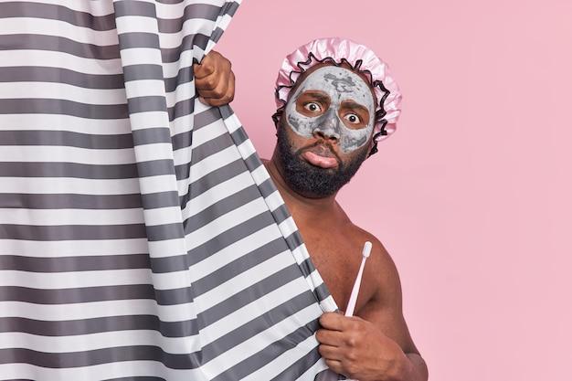 두꺼운 수염을 가진 의아해하는 남자는 영양 점토 마스크를 착용하고 목욕 모자를 착용하고 칫솔을 쥐고 샤워 커튼 뒤에 알몸을 숨기고 분홍색 벽에 격리 된 매일 위생 절차를 거칩니다.