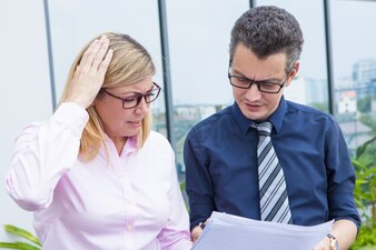 Puzzled mature businesswoman displeased with report data while discussing it