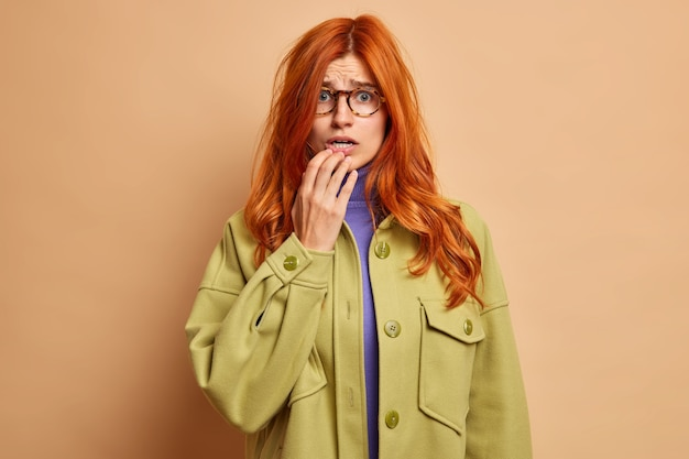 Puzzled nervous european woman with ginger hair afraids of something has anxious look dressed in fashionable jacket.