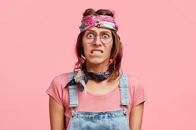 Puzzled nervous hippy woman bites lower lips, looks in embarrassement, worries before important event, wears stylish bandana and dungarees
