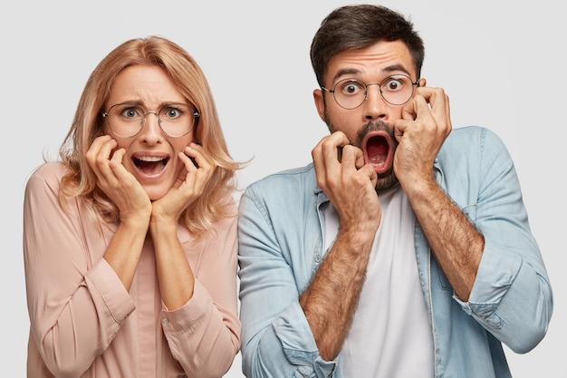 Puzzled nervous scared woman and man business partners react on lowering sales and having financial debts