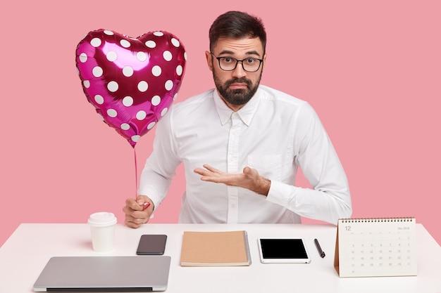 Озадаченный офисный работник имеет тайного поклонника, спрашивает, чья это валентинка, держит воздушный шар, одет в белую рубашку.
