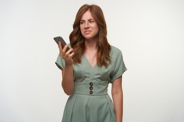 Озадаченная симпатичная женщина с вьющимися рыжими волосами, держащая смартфон в руке, смотрит на экран с растерянным лицом, позирует