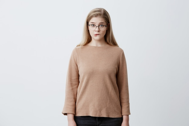Puzzled pretty woman wearing eyeglasses with straight blonde hair biting her lower lip looking with surprise into camera. human face expressions and emotions. european girl shocked
