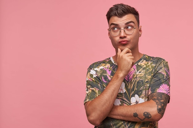 Puzzled pretty young tattooed man in flowered t-shirt, looking aside with folded lips and raising eyebrows, being discouraged, isolated