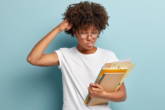 La pupilla interrogata perplessa si gratta la testa, guarda con dubbio e espressione dispiaciuta ai documenti, trasporta quaderno a spirale e libro, cerca di trovare una risposta, vestito con una maglietta bianca casual, isolato sul muro blu