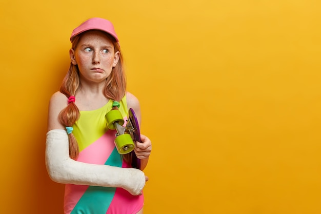Puzzled redhead girl holds longboard under arm, poses with skate and broken hand in cast, has unlucky day and looks displeased aside, isolated on yellow wall, got injured after doing trick
