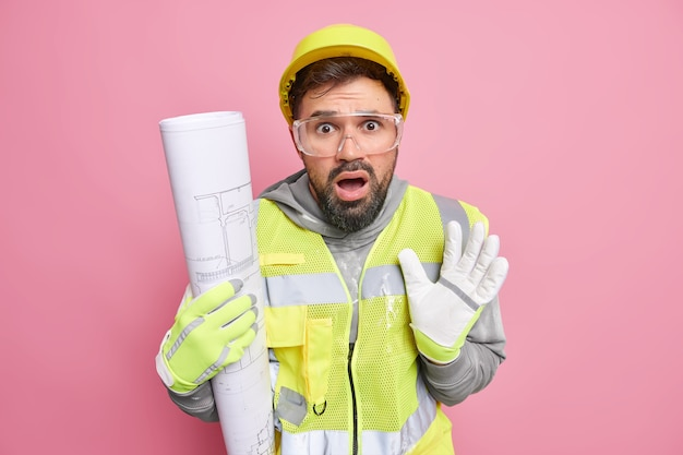Puzzled scared bearded man engineer holds architectural blueprint comes on building site being afraid of something wears hardhat reflective vest and gloves poses against pink studio wall.